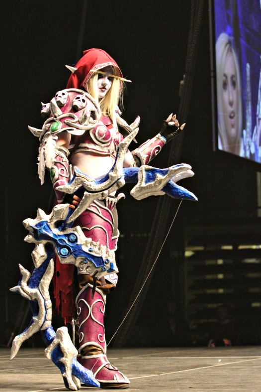 A cosplayer costumed as a night-elf hunter poses as Jessica Nigri looks on agog.